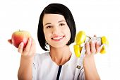 Dietista mujer sosteniendo la manzana y pesas con cinta métrica