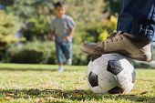 Child running for the football under his fathers foot in the park
