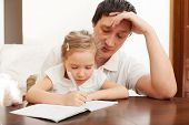 Father helping daughter doing homework. Parent with child writing