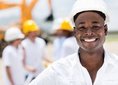 Happy male engineer at a construction site smiling