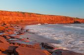 The rocky shore of Prince Edward Island at daybreak illuminating the cliffs and rocks bright red.