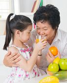 Asian family drinking orange juice. Happy Asian grandchild sharing cup of fresh squeeze fruit juice with grandmother at home.