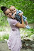 Happy Mom And Baby Boy Hugging And Laughing. The Concept Of Childhood And Family. Beautiful Mother A