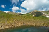 stock photo of swales  - Small mountains with Colorful Lake and dark blue sky and clouds in Kyrgyz mountains
