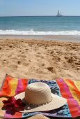 foto of sand lilies  - beach hat and flower on towel  in the sand with sailboat in the background - JPG