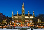 stock photo of illuminated  - Festively illuminated Christmas fair and city hall in Vienna - JPG