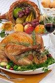 image of horn plenty  - Garnished roasted turkey on fall festival decorated table with horn of plenty and red wine - JPG