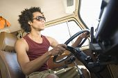 Low angle view of a young man driving campervan