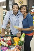 Portrait of a smiling couple standing with grocery shopping in supermarket aisle