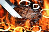 stock photo of ribs  - Delicious juicy rib eye steak on a barbecue grill with flames - JPG