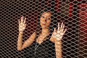 stock photo of kidnapped  - Young woman behind a metal fence - JPG