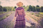 foto of lavender field  - Woman in purple dress and hat with basket in lavender field  - JPG