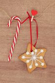 Christmas gingerbread snowflake cookie hanging on a line with rock cane candy bar.
