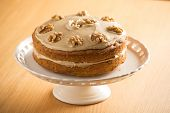 picture of custard  - Beautifully presented Coffee and Walnut cake on a white cake stand