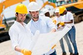 foto of real-estate-team  - Team of architects at a building site looking at blueprints - JPG
