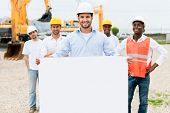 image of real-estate-team  - Architect holding a banner at a building site - JPG