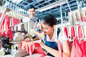 Asian Seamstress or worker in a textile factory sewing with a industrial sewing machine, she is very
