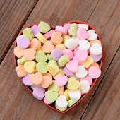High angle view of a heart shaped box filled with Valentine's Day Candies. The box in the middle of a rustic wood background. The heart shaped candy is blank and ready for your message.