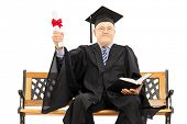 Mature man in graduation gown seated on bench holding a diploma and book isolated on white background