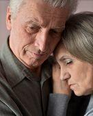 Sad elder couple on brown background