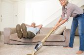 Man resting on couch while woman using vacuum on area rug in the living room at home