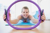 Portrait of a smiling sporty young woman with exercising ring in fitness studio