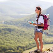 Young, Beautiful Girl With A Backpack and map on mountain