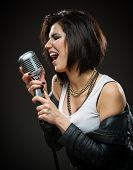 Half-length portrait of female rock singer wearing black jacket and holding microphone on grey background. Concept of music and rave