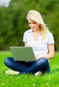 Attractive female student with silver laptop sitting on the grass in the summer park