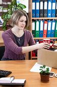 Woman Collects Things In A Cardboard Box In The Workplace