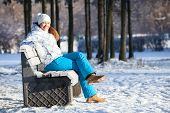 Happy Young Woman Sitting On Bench In Winter Outdoors, Copyspace