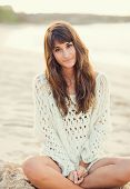 Beautiful young woman in sweater on the beach at sunset, Fashion lifestyle warm backlit sunlight