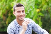 stock photo of addiction to smoking  - Man smoking an electronic cigarette outdoors - JPG