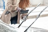 Woman cleaning car wipers from snow