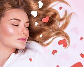 Closeup portrait of romantic fashion model lying down with closed eyes, beautiful long hair with red