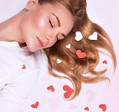 Portrait of sweet female lying down on white floor with closed eyes, sleeping and see romantic dream
