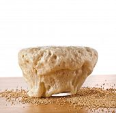 Rising Yeast Dough in bowl close up isolated on wooden table background