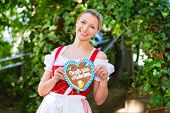 Young woman in traditional Bavarian clothes or tracht with a gingerbread souvenir heart in beergarde