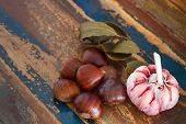 Chestnut, Garlic And Bay Leaf On Wooden Table