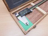 stock photo of vernier-caliper  - Metal vernier caliper in wooden box package closeup on wood table - JPG