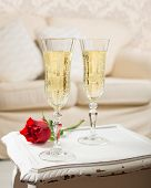 Two glasses of champagne with a red rose