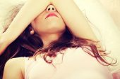 image of sad eyes  - Sad woman is lying in bed with her arm on head and eyes - JPG