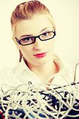 Young blond woman in black glasses and white shirt with cables and wires. Blond girl looking sceptic