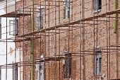 picture of scaffold  - Scaffolding covering old brick building under restoration - JPG