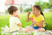 Little girl and boy are blowing soap bubbles, outdoor shoot