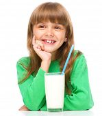 Cute little girl is drinking milk, supporting her head with hand, isolated over white