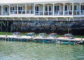Multi Colored Picnic Tables On Pier Beneath Hotel