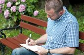 Man Writing In Notepad