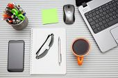 Office Desk With Laptop With Business Accessories And Cup Of Tea