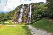 Double falls in mountains of northern Italy. Parallel streams of water on a green overgrown hillside